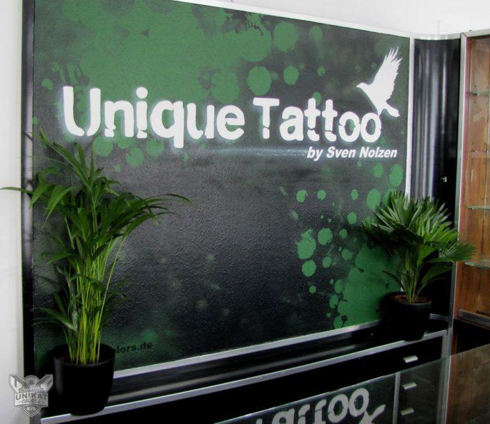 Unique tattoo Logo auf Wand im Eingang